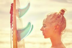 Beautiful girl surfer with a board at sunrise. Summer vacation at sea, healthy lifestyle. royalty free stock photo