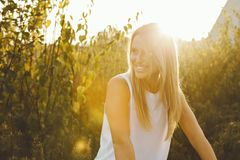 Beautiful girl surrounded by flowers at sunset. Beautiful, happy girl is smiling, surrounded by flowers in a city at sunset Royalty Free Stock Images
