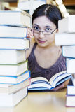 Beautiful girl surrounded by library books Royalty Free Stock Photography