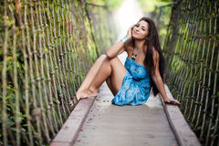 Beautiful girl on the suspended wooden bridge Stock Photos