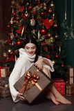 Beautiful girl in sweater sitting at the Christmas tree. Gifts, new year. Beautiful girl in sweater sitting at the Christmas tree. Gifts, New year, Christmas Stock Image