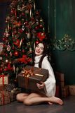 Beautiful girl in sweater sitting at the Christmas tree. Gifts, new year. royalty free stock photos