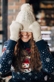 Beautiful girl in sweater with snowmen pulled a cap over eyes. Beautiful girl in hat Christmas close-up,Christmas photo shoot,brunette in Christmas sweater royalty free stock photography