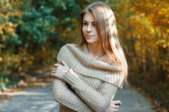 Beautiful girl in a sweater standing in autumn park Royalty Free Stock Photos