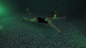 Beautiful girl swim underwater into night waterpool with lights. Dark Night. Beauty young woman submerged under water in swimming pool with lights. Underwater stock video