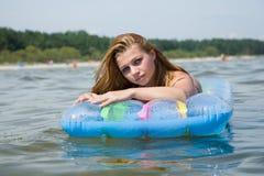 Beautiful girl swimming on mattress royalty free stock photography