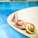 Beautiful girl at swimming pool with hat over head.  Royalty Free Stock Images