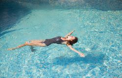 Beautiful girl swimming in the pool on her back.  Royalty Free Stock Images