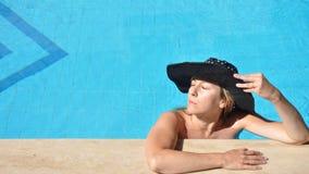 Beautiful girl in a swimming pool, wearing a mask. Beautiful girl in a swimming pool, wearing a hat Stock Photo