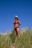 A beautiful girl in a swimming suit stands in a high grass Stock Photography