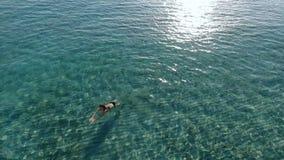 Beautiful girl swims in blue ocean stock video