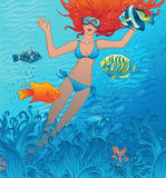 Beautiful girl swims with tropical fishes Stock Image