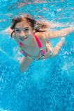 Beautiful girl swims underwater in pool Royalty Free Stock Photos
