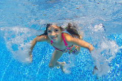 Beautiful girl swims underwater in pool Royalty Free Stock Images