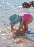 Beautiful girl with swimsuit and hat playing on the riverbank with water royalty free stock image