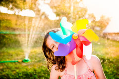 Beautiful girl in swimsuit hiding behind pinwheel, summer garden Royalty Free Stock Images