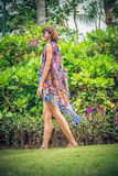 Beautiful girl in a swimsuit and pareo posing on flower background in nature of Bali island, Indonesia. Royalty Free Stock Photography