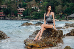 Beautiful girl in a swimsuit posing on rocks in the sea. Against the background of hotels bungalows. royalty free stock images
