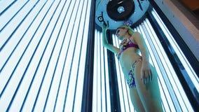 Beautiful girl in swimsuit at solarium. stock video
