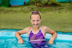 Beautiful girl in a swimsuit swims in the pool. By the summer stock photography