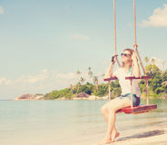 Beautiful girl on a swing against the background tropical seasca Royalty Free Stock Photography