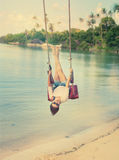 Beautiful girl on a swing against the background tropical seasca Royalty Free Stock Images