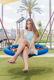 Beautiful girl on a swing on the park Stock Photos