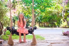 Beautiful girl swinging on a swing in cozy lovely Stock Image