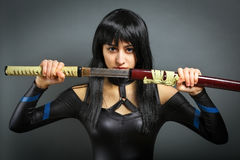 Beautiful girl with sword on grey background. Royalty Free Stock Photo