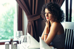 Beautiful girl at table. Beautiful girl sitting at restaurant table looking at someone Stock Photos