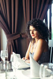 Beautiful girl at table. Beautiful girl sitting at restaurant table smiling Royalty Free Stock Image