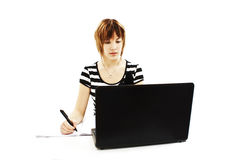 Beautiful girl at table, studying Stock Images