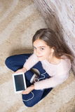 Beautiful girl with  tablet. Preteen child playing on ipad sitting on a carpet at home Royalty Free Stock Photography