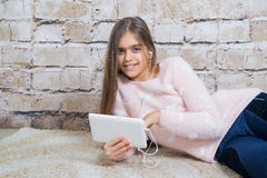 Beautiful girl with tablet. Preteen child playing on ipad sitting on a carpet at home.  Girl listening to music on headphones Royalty Free Stock Photography