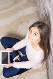 Beautiful girl with  tablet. Teen girl playing on tablet pc laying down on a white carpet at home Stock Photo
