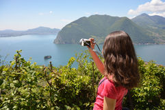 Beautiful girl take a photo with a mirrorless to the landscape of lake and mountains in sunny day. Travel healthy lifestyle concep Stock Photos