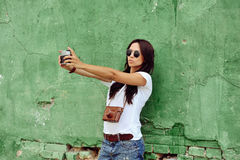Beautiful girl taken pictures of her self on vintage camera Royalty Free Stock Image