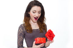 Beautiful girl taken by surprise opening gift box. On white background royalty free stock images