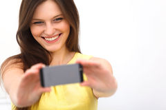 Beautiful girl taken taking selfie self-portrait with phone. Beautiful girl taken taking selfie self-portrait with camera phone royalty free stock photo