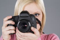 Beautiful girl takes photo with DSLR Royalty Free Stock Images