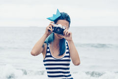 Beautiful girl takes a photograph on beach Royalty Free Stock Image