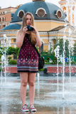 Beautiful girl takes pictures in a fountain Royalty Free Stock Photography