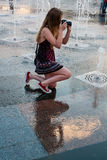 Beautiful girl takes pictures in a fountain royalty free stock photo