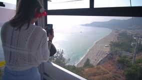 The girl is riding in the funicular and is holding a phone. Beautiful girl takes pictures on the phone of the beach of Cleopatra in Alanya stock footage
