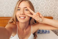 Beautiful girl takes selfie showing two fingers in camera wakes royalty free stock image