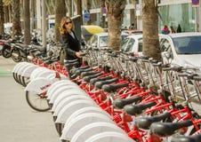 Beautiful girl taking a bike of row on the street, in Barcelona, stock image
