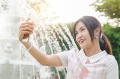 Beautiful girl taking her photo by phone outdoor Royalty Free Stock Photos