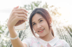Beautiful girl taking her photo by smart phone Stock Images