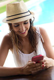 Beautiful girl taking a mobile phone at the swimming pool. Royalty Free Stock Photos