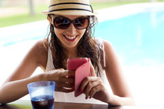Beautiful girl taking a mobile phone at the swimming pool. Stock Image